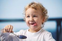 Breakfast. Portrait of the little boy eating yogurt Stock Images
