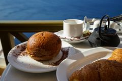 Breakfast with Aegean sea view and morning sunlight including hot tea, croissant and chocolate brioche bun on white marble table. Next to olive green balcony stock image
