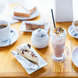 Breakfast or afternoon snack with creamy cappuccino and cake on wooden table. Breakfast or afternoon snack with creamy cappuccino and cake on wooden table Royalty Free Stock Photo