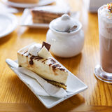 Breakfast or afternoon snack with creamy cappuccino and cake on wooden table. Breakfast or afternoon snack with creamy cappuccino and cake on wooden table Royalty Free Stock Photography