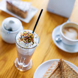 Breakfast or afternoon snack with creamy cappuccino, sandwich and cake on wooden table. Breakfast or afternoon snack with creamy cappuccino, sandwich and cake Stock Photography