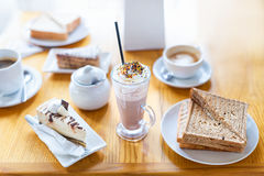 Breakfast or afternoon snack with creamy cappuccino, sandwich and cake on wooden table. Breakfast or afternoon snack with creamy cappuccino, sandwich and cake Royalty Free Stock Photography