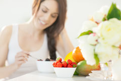 Breakfast Arrangement. Smiling woman at breakfast. Arranged fresh fruit. Strawberries as foreground Stock Image