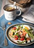 Breakfast. Arugula salad with salmon and parmesan, a cup of tea with lemon. Rustic style. Food photo stock photo