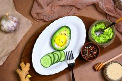 Breakfast avocado baked with egg, sliced cucumber, pepper, garlic, ginger the concept of healthy eating, copy space, top view set royalty free stock image