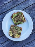 Breakfast: avocado toast with dukkah on plate on wooden table Royalty Free Stock Photos