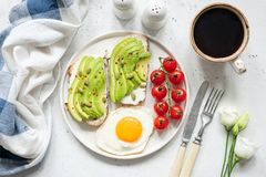 Breakfast avocado toast with egg and coffee cup. Breakfast avocado toast with fried egg, cherry tomatoes, cup of coffee and white flowers. Breakfast in bed stock images