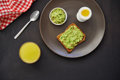 Breakfast with avocado toast. Orange juice and boiled egg. top view stock image