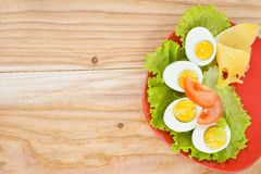 Breakfast background. Hard boiled eggs, sliced in halves, salad, tomatoes and cheese on the red plate. Royalty Free Stock Photography