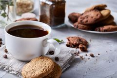 Breakfast background with mug of fresh coffee, homemade oatmeal cookies, grind coffee. Breakfast background with porcelain mug of fresh black coffee, homemade Stock Image