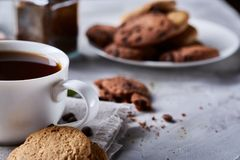 Breakfast background with mug of fresh coffee, homemade oatmeal cookies, grind coffee. Breakfast background with porcelain mug of fresh black coffee, homemade Stock Images