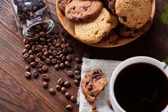 Breakfast background with mug of fresh coffee, homemade oatmeal cookies, grind coffee. Breakfast background with porcelain mug of fresh black coffee, homemade Stock Photography