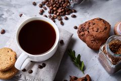 Breakfast background with mug of fresh coffee, homemade oatmeal cookies, grind coffee. Breakfast background with porcelain mug of fresh black coffee, homemade Stock Photo