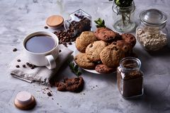 Breakfast background with mug of fresh coffee, homemade oatmeal cookies, grind coffee. Breakfast background with porcelain mug of fresh black coffee, homemade Stock Photos