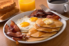 Breakfast with bacon, eggs, pancakes, and toast. A delicous home style breakfast with crispy bacon, eggs, pancakes, toast, coffee, and orange juice stock photo