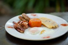 Breakfast - bacon, eggs, sausage,tomato and banana. Egg, bacon, lamb sausage, fried tomato and banana on a white plate served fro breakfast Royalty Free Stock Photography