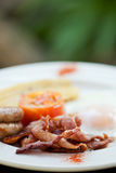 Breakfast - bacon, eggs, sausage,tomato and banana. Egg, bacon, lamb sausage, fried tomato and banana on a white plate served fro breakfast Stock Photo