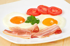 Breakfast with bacon,  fried eggs and slices tomatoes Royalty Free Stock Photo