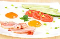 Breakfast with bacon, fried eggs and slices tomatoes Stock Photos
