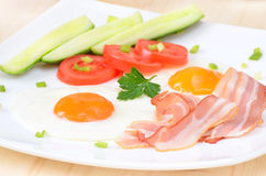 Breakfast with bacon, fried eggs and slices tomatoes Royalty Free Stock Image