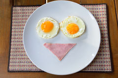 Breakfast with bacon and fried eggs on white plate Stock Photo