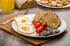 Breakfast- bacon, sausage, bread and eggs Royalty Free Stock Photos