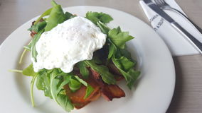 Breakfast. Bacon, smoked salmon  and poached egg meal with a salad Royalty Free Stock Images