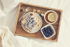 Breakfast in bad,  tray with belgian waffles with blueberry and. Cup of lemon tea, toned, top view Royalty Free Stock Photos