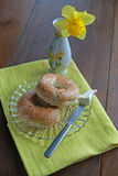 Breakfast bagels and cream cheese. Two bagels and cream cheese with dandelion in a vase on yellow napkin Stock Photos