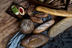 Breakfast and baked bread concept. Fresh fragrant bread and egg on wooden table. Fresh bread and coffee and wheat on wood black royalty free stock images