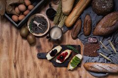 Breakfast and baked bread concept. Fresh fragrant bread and egg on wooden table. Fresh bread and coffee and wheat on wood black stock image