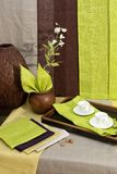 Breakfast bar. Two coffee cups on the breakfast tray, with green and brown linen napkins, and wooden vase with flower branches stock images