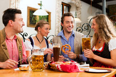 Breakfast with Bavarian white veal sausage. Group of young men and women in traditional Bavarian Tracht having a breakfast with white veal sausage, pretzel, and Royalty Free Stock Image
