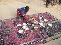 Breakfast on the beach. Madagascar: malagasy man has prepared the breakfast on the beach for the tourists.  Madagascar's tourist attractions include its beaches Royalty Free Stock Images