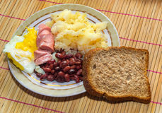 Breakfast. Beans, sausage, potatoes, bread and scrambled eggs. Close-up plates of food on the table with bamboo floors Royalty Free Stock Photography