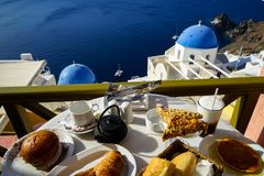 Breakfast with beautiful Aegean sea view, boat and Oia church including pancake, baguette, croissant, hot tea, chocolate brioche. Bun and fruity cereal bar on stock photos