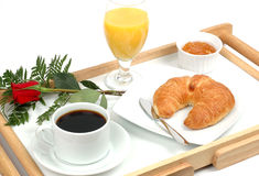 Breakfast In Bed. Breakfast tray with coffee, orange, juice, croissant, marmalade and rose Royalty Free Stock Photo