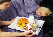 Breakfast in bed. Young male serving a breakfast in bed to woman Stock Image