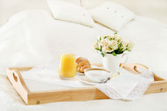 Breakfast in bed. With coffee, orange juice and croissant on a tray