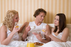 Breakfast in bed. Threesome having a breakfast in bed Royalty Free Stock Image