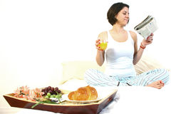 Breakfast in bed. Smiling woman sit in newspaper and orange juice in hand and having breakfast in bed royalty free stock image