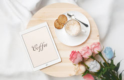 Breakfast in bed with cappuccino, roses and tablet Royalty Free Stock Images
