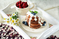 Breakfast in bed: chocolate pancakes with yogurt sauce and berries Stock Image