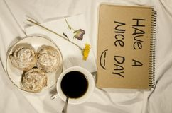 Have a nice day. Breakfast in bed with coffee, biscuits and flowers. Have a nice day concept. Start your morning with a smile on your face royalty free stock image