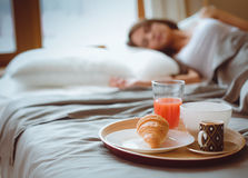 Breakfast in bed with coffee and croissant for attractive young woman Stock Image