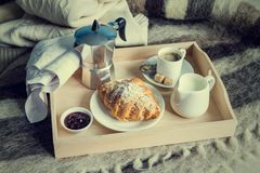 Breakfast in bed - coffee, croissant, milk on tray. Wool blanket, toned Stock Image