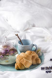 Breakfast in bed. Cup of tea and croissants wooden tray. Breakfast in bed Valentine`s day breakfast in bed, Mother`s day or Women`s day concept Stock Photos