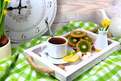 Breakfast in bed with a Cup of tea with lemon. Biscuits and an alarm clock Stock Images