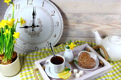 Breakfast in bed with a Cup of tea with lemon. Biscuits and an alarm clock Stock Photos