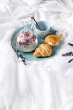 Breakfast in bed. Enjoying a good cup of tea in the morning, teapot of flower tea with Fresh croissants on a plate . Valentine`s day breakfast in bed, Mother`s Stock Photos